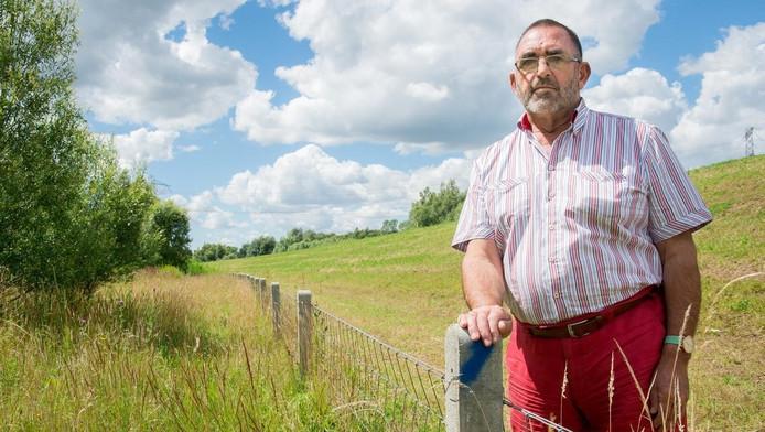 Nico Kooij bij het hek dat vluchtende reeën in de weg staat. Op zes plaatsen worden nu gaten in het hek gemaakt.