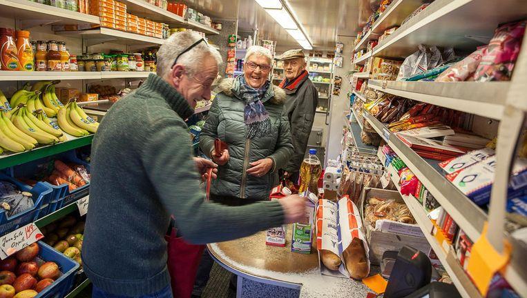 Adolf Schaap helpt in zijn rijdende winkel inwoners van Ulrum aan de dagelijkse boodschappen. Beeld Harry Cock