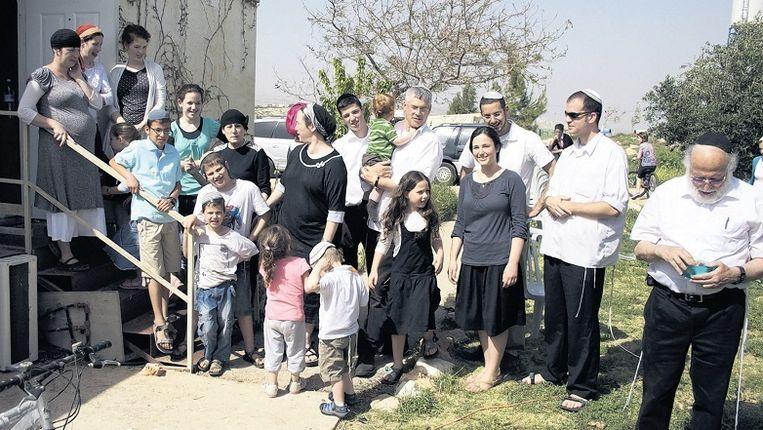 Tati Gutman (linksboven op de trap in grijze jurk) met haar familie en vrienden. 'We zijn hier uit overtuiging komen wonen.' Beeld Laurens Samsom