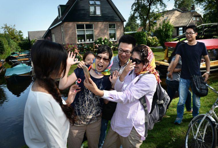 Chinese toeristen in het Overijsselse Giethoorn. Sommige vakantiegangers denken dat de plaats een museumdorp is en behandelen bewoners als acteurs.  Beeld Marcel van den Bergh