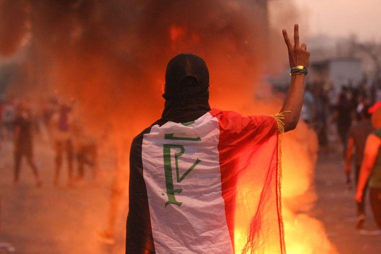 Een demonstrant met de Iraakse vlag over zijn schouders maakt het vredesteken in Bagdad.