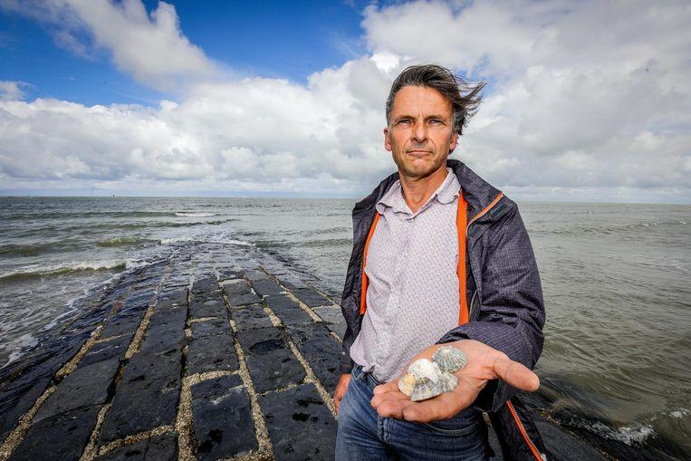 Jan Seys van het Vlaams Instituut voor de Zee met een schaalhoren, een soort zeeslak.