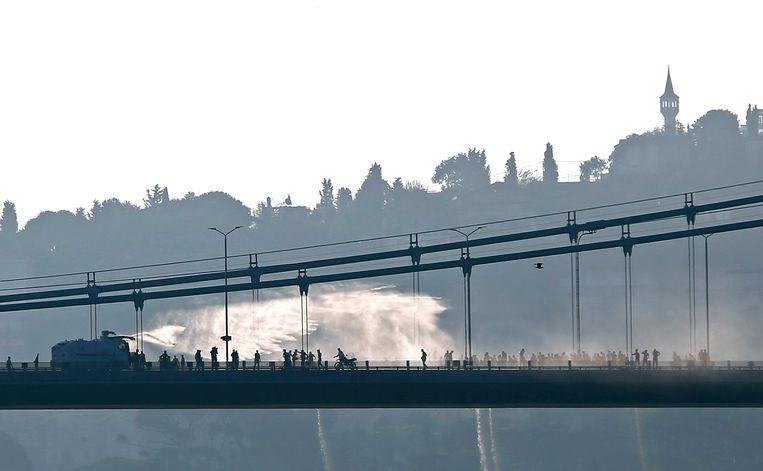 Een waterkanon van de politie op de Bosporusbrug jaagt demonstranten weg. Beeld REUTERS