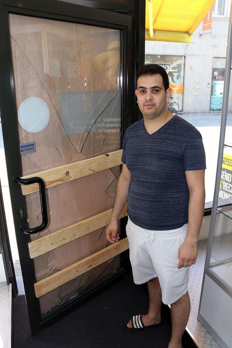 Mohamed Hatite bij zijn kapotte deur.