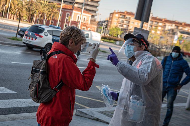 Een vrouw krijgt in het treinstation van Girona een mondmasker van een civiele agent.