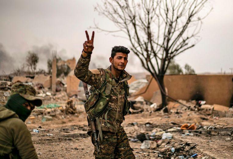 Soldaten van de Syrische Democratische Strijdkrachten, die IS verdreven, poseren trots op het slagveld.