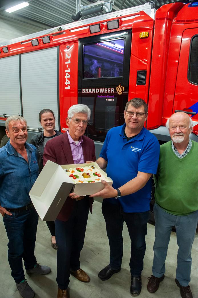 Burgemeester Pommer overhandigt, bijgestaan door leden van het bestuur Gedenkplaats Haaren, een taart aan Albert van de Wiel, commandant brandweer Haaren, als dank voor de inzet bij de brand bij Haarendael.