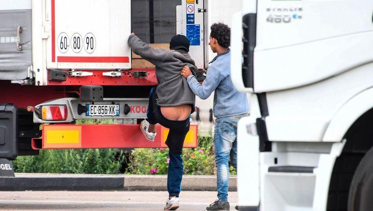 Migranten klimmen in Calais in een truck. Chauffeurs van de Groningse vervoerder Reining zouden door 'inklimmers' zijn bedreigd met stokken en met stenen zijn bekogeld Beeld afp