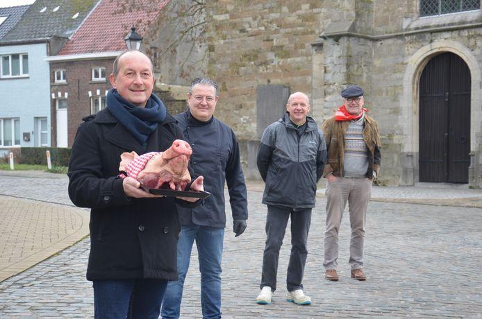 Kris Van der Perre, voorzitter van de Heemkundige Kring Iddergem, slagers Kris en Jos en volksfiguur Gerrit Borreman aan de kerk van Iddergem met de varkenskop.