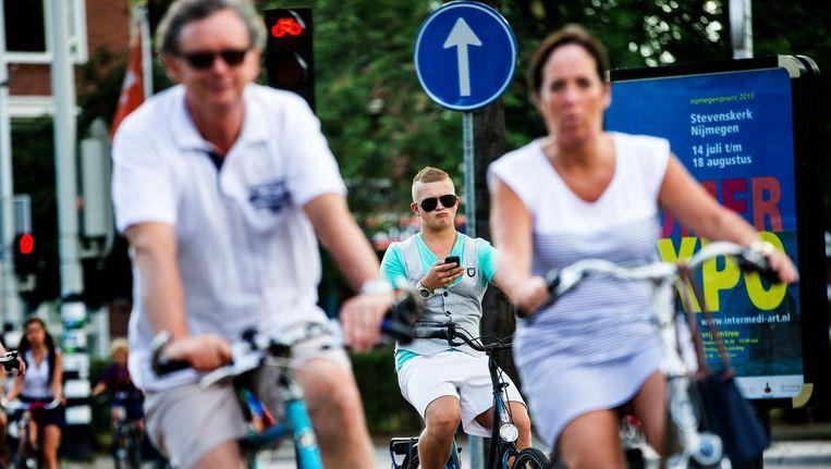 Een fietser gebruikt zijn mobiele telefoon op de fiets op het Nijmeegse Keizer Karelplein. Whatsappen of internetten op de fiets leidt tot tientallen ongelukken per jaar. Beeld anp