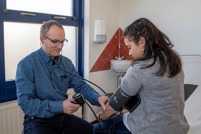 De Bergse huisarts Martijn Raat meet de bloeddruk bij een patiënt. Er moet dringend wat gebeuren aan de zware werklast van huisartsen, vindt Raat.