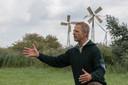 Terreinbeheerder Rob Timmerman in het natuurgebied Gruttoveld, met op de achtergrond twee van de vier windmolentjes die water in het gebied moeten  pompen.