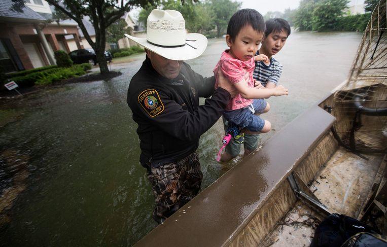 Een sheriff in Fort Bend County helpt bij een evacuatie. De autoriteiten hebben de evacuatie bevolen van 55.000 mensen in de regio ten zuidwesten van Houston. Beeld AP