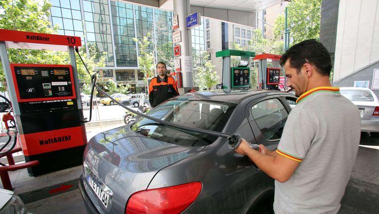 Een medewerker van een pompstation in de Iraanse hoofdstad Teheran vult een auto met brandstof. Beeld afp