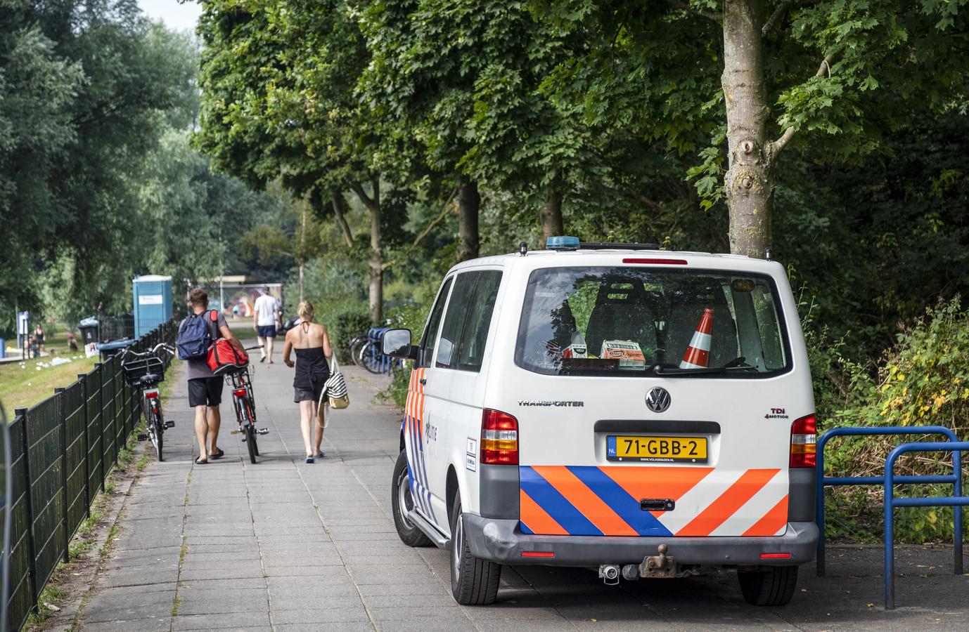 Een politiebusje aan het Nieuwe Meer in natuurgebied De Oeverlanden, waar een dag eerder een schietpartij heeft plaatsgevonden die een 24-jarige man het leven kostte.