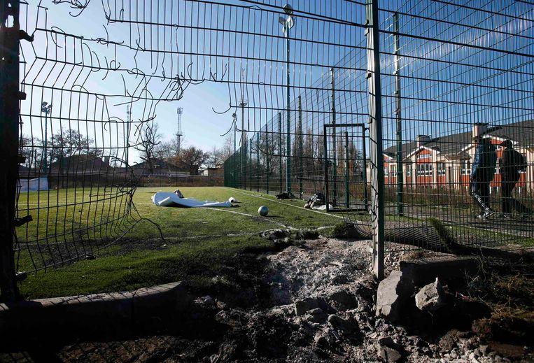 Een bomkrater op een voetbalveld bij een school in Donetsk, in Oost-Oekraïne. Archieffoto.