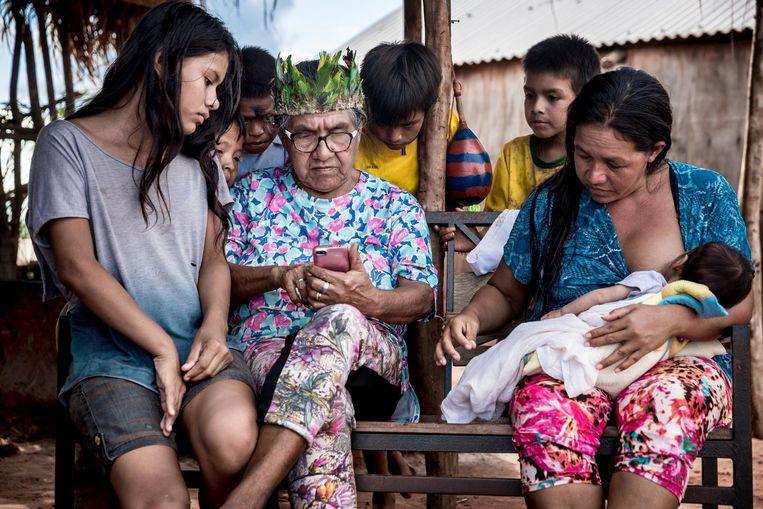 Julia Cavalheiro laat iets aan haar kleinzoon zien op haar mobiele telefoon. Beeld Leonardo Wen
