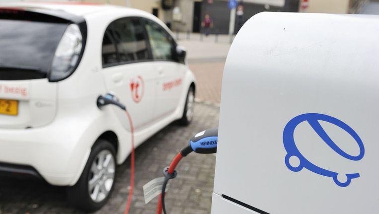 Een elektrische auto wordt opgeladen bij een oplaadpunt. Beeld anp