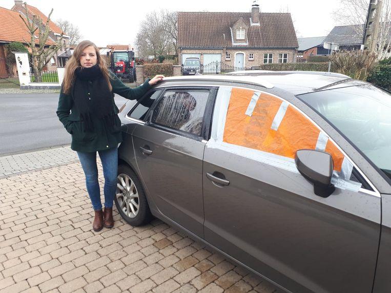 Sandrien bij haar gehavende auto: de achterste ruit sneuvelde vorige week, de voorste ruit donderdag.