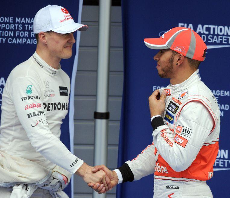 Michael Schumacher schudt de hand van Lewis Hamilton na de kwalificatie voor de GP van China in 2012. Beeld Hollandse Hoogte / AFP