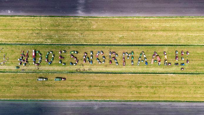De tractoren die samen de kreet #doesnormaal!!! vormen in een weiland  horen bij boeren die het meer dan zat zijn. Het is een 'last minute'-actie op de zondagmiddag.