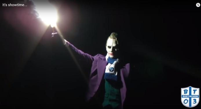 Screenshot uit de video, die de Joker toont die een fakkel afsteekt op De Vijverberg.