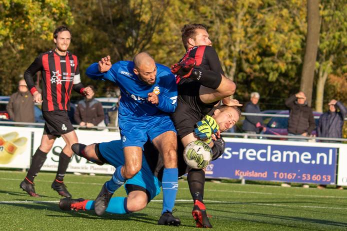 RBC-speler Marouane Hamdoune (blauw shirt) mist de bal, maar ontwijkt ternauwernood de schoen van Gastel-verdediger Matthijs Nagtzaam. Ook Gastel-doelman Coert Doomen mengt zich in de strijd.