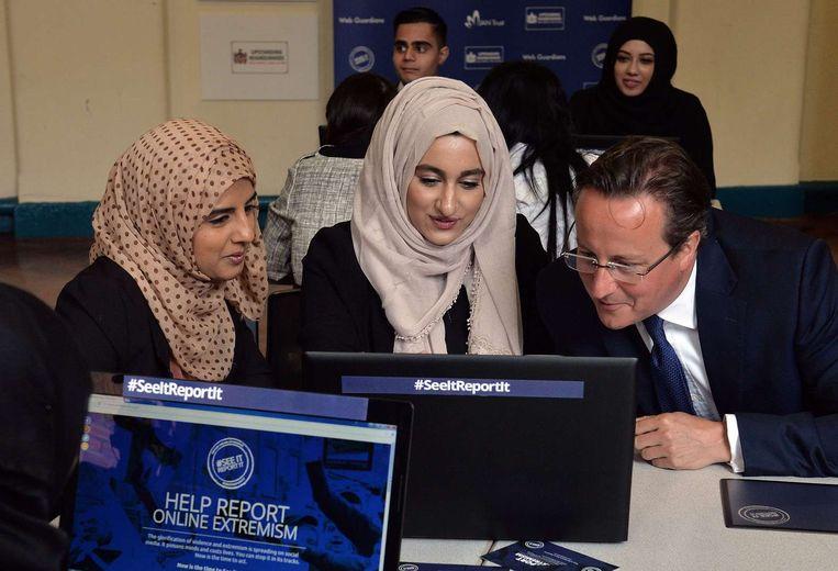 De Britse premier David Cameron bekijkt met Aysha Iqbal Patel (L) and Zahra Qadir een laptop tijdens een workshop over het rapporteren van verdacht gedrag online. Beeld afp