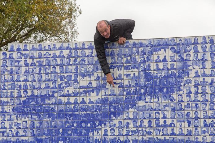 Henk Angenent wijst naar zijn eigen beeltenis op het Tegeltjesbruggetje over de Murk, het officiële monument voor de Elfstedentocht