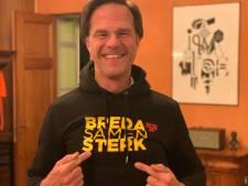 Premier Mark Rutte fietst naar corona-overleg met hoody uit Breda