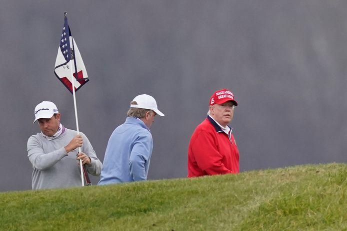 Donald Trump (in het rood) tijdens een potje golf gisteren.
