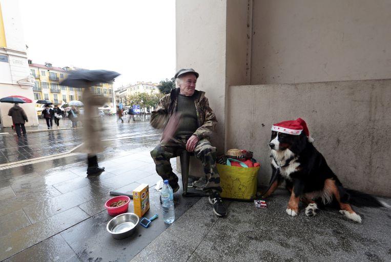 Een dakloze man met zijn hond in het centrum van Nice.