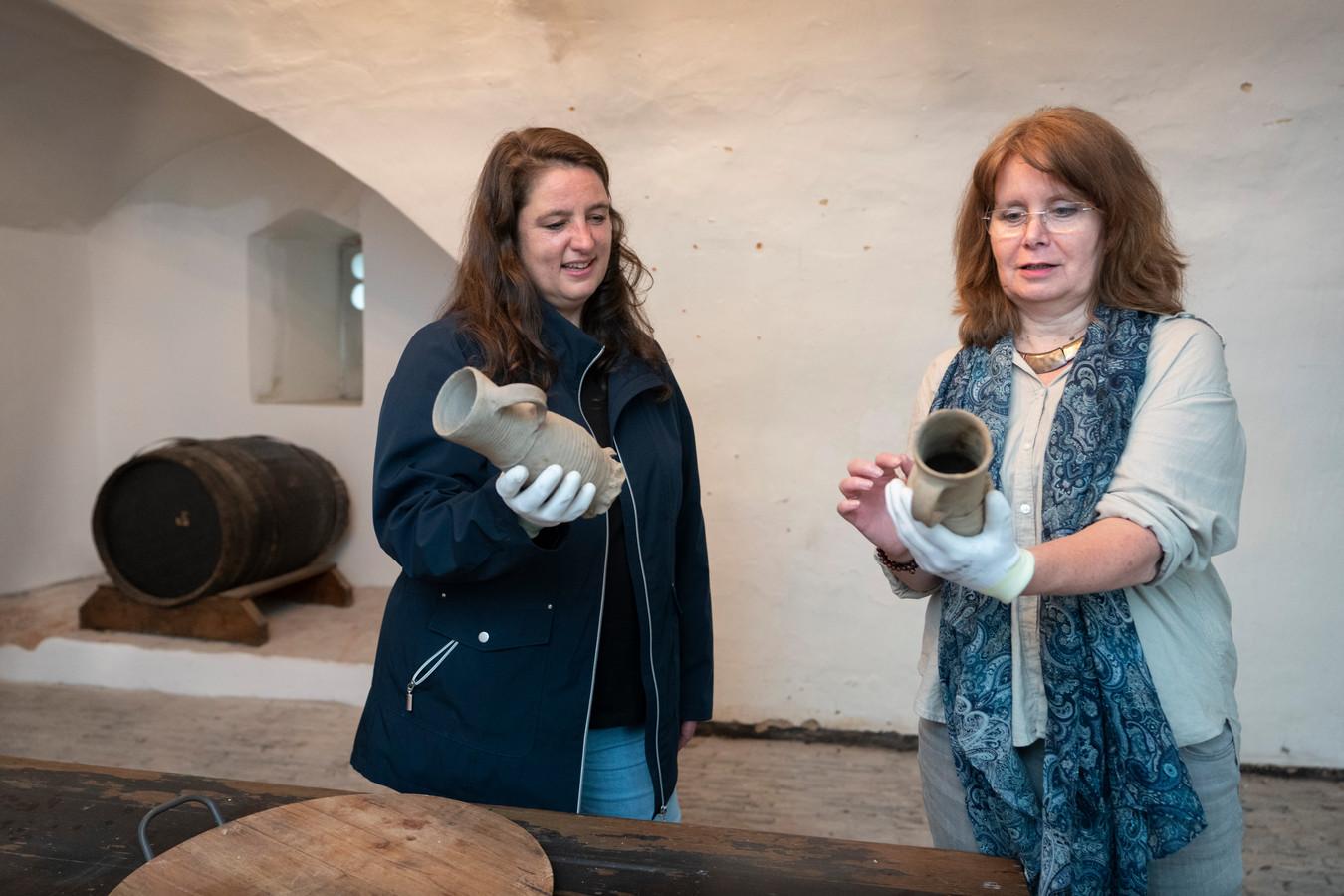 Annette Zeelenberg (links)  en conservator Marieke Knuijt in de bierkelder van kasteel Ammersoyen met bierpullen die vrijwel ongeschonden in de kasteelgracht zijn gevonden.
