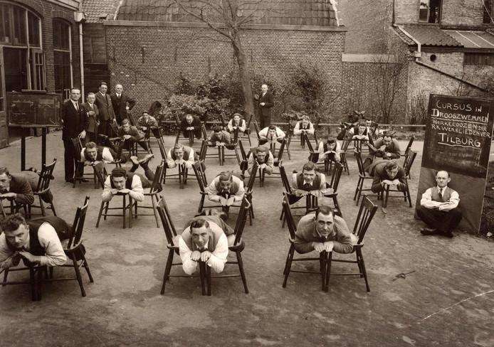 Cursus 'droogzwemmen' voor werklozen in de achterliggende tuin (1936) van de Tuinstraat 66/68/70, vroeger het pand van de RK Tilburgsche Gildenbond. Het werk van de bond had ook een opvoedkundig tintje, ter 'verheffing' van de katholieke volksklasse.