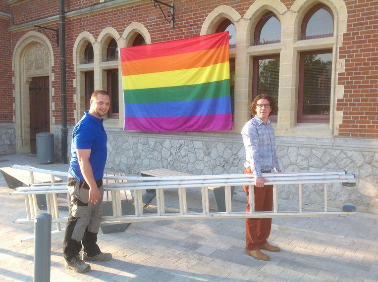 Ruben De Gusseme en Filip Michiels (Open Vld) hijsen de vlag aan het gemeentehuis van Oosterzele.