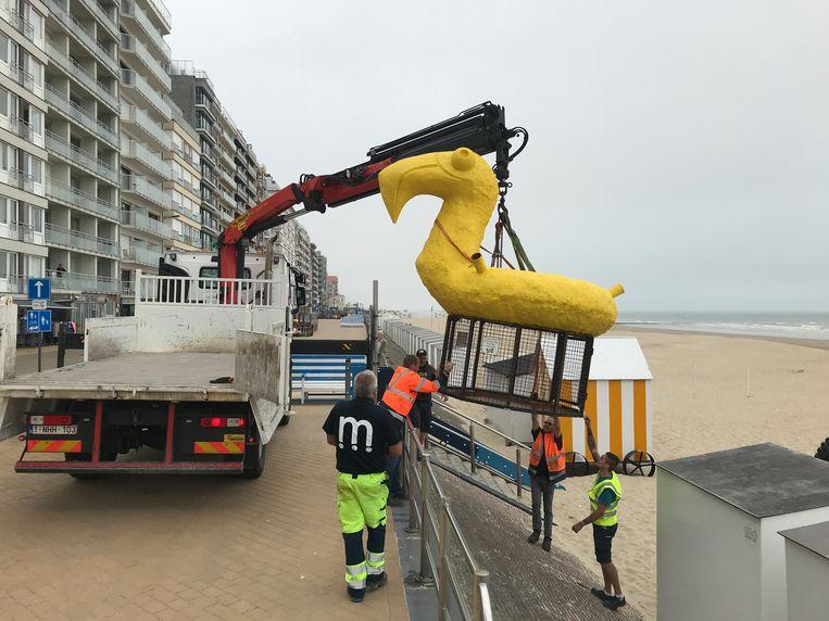 De werkliedenploeg van de gemeente plaatsen de kunstige vuilnisbak op het strand van Westende