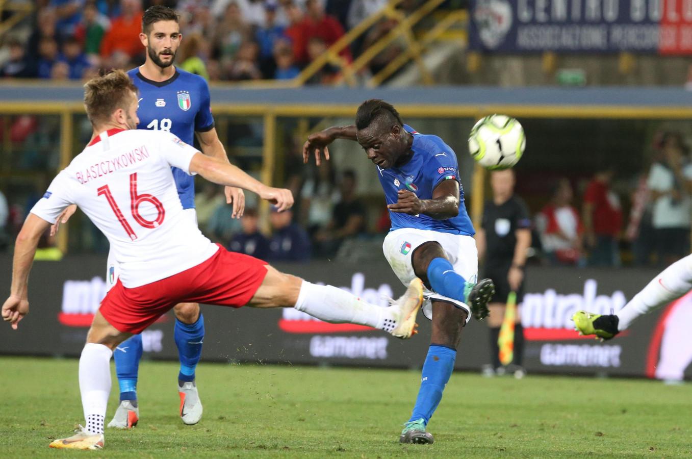 Mario Balotelli haalt uit tegen Polen. Links Jakub Blaszczykowski.