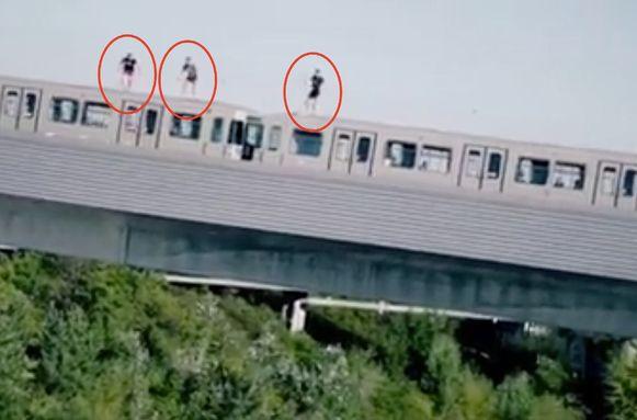 Van op het dak van rijdende metro springen de drie naar beneden.