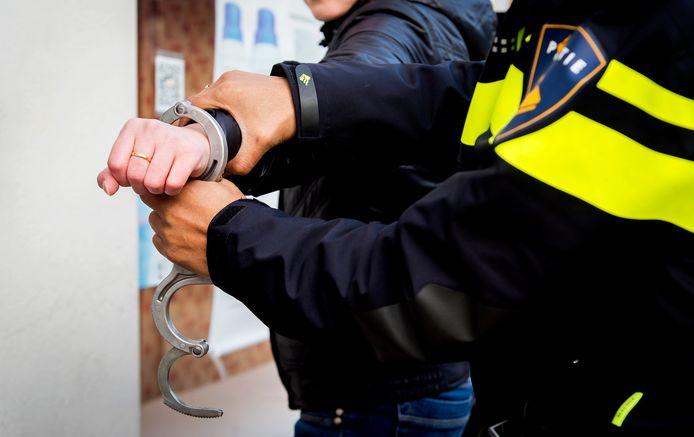 Een politieagent slaat een verdachte in de boeien.