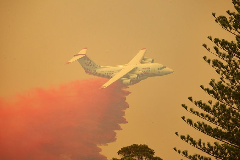 Een blusvliegtuig dropt brandwerend product in Harrington, New South Wales