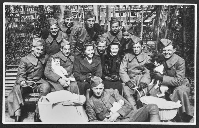 Groepsportret van rekruten met een aantal meisjes. Paul Bijnen  staat rechts op de foto met poppenwagen.