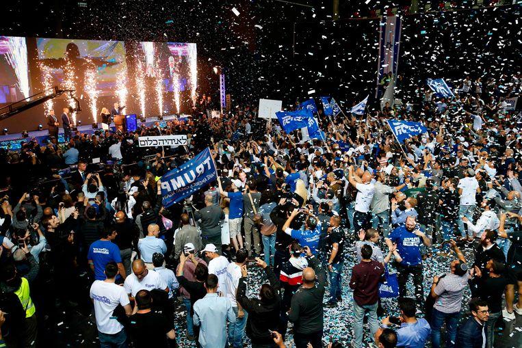 Likud-aanhangers vierden dinsdag al feest in Tel Aviv, ook al was de verkiezingsuitslag nog onbeslist. Op het podium premier Netanyahu. Beeld AFP