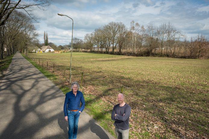 Henk Osinga en Jurrian Bijsterbosch (rechts) bij het weiland dat eigenaar Hans Brouwer vol wil leggen met zonnepanelen.