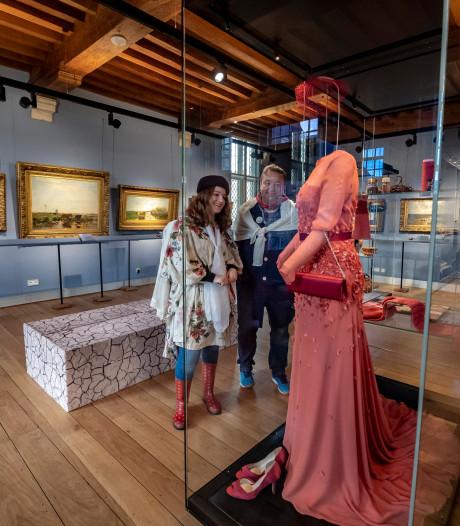 Met een gordijn om kijken naar de japon van koningin Máxima in Bergen op Zoom