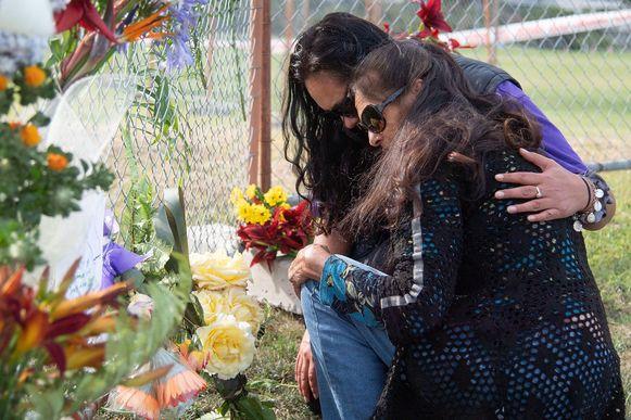 Twee vrouwen leggen bloemen neer in Whakatane.