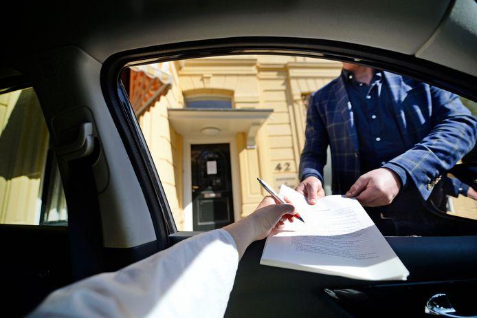 Sommige cliënten van notaris Geert Venema van Hofsteenge Wesseling geven, uit angst voor corona, er de voorkeur aan via het autoraam te tekenen.