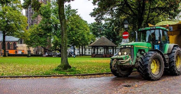Tractor met zwaarbeladen aanhanger neemt de Hoge Zij langs de Vrijthof in Hilvarenbeek.