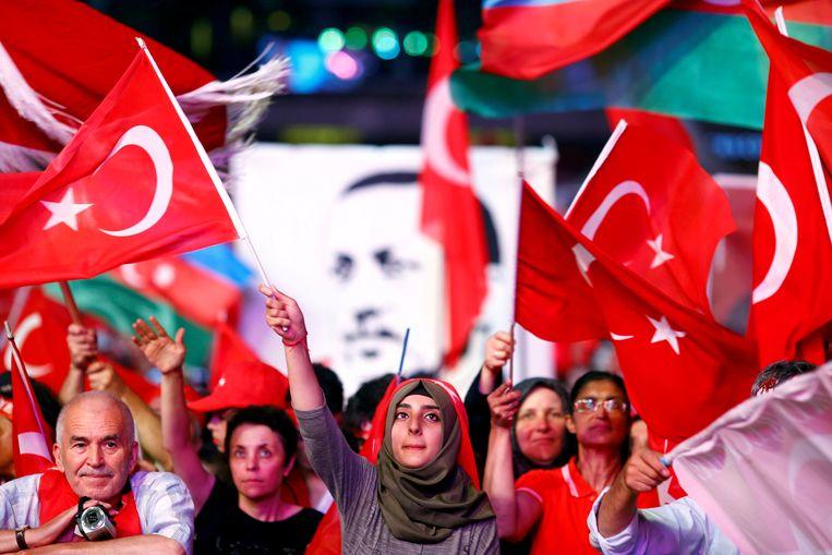 Aanhangers van de Turkse president Erdogan zwaaien met vlaggen.