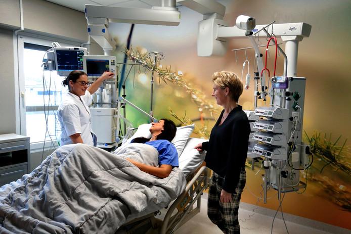 Margijske van Roest (links) en Karin Koedam staan samen aan het bed in een van de nieuwe kamers op de IC. Elk heeft een fotowand gekregen.