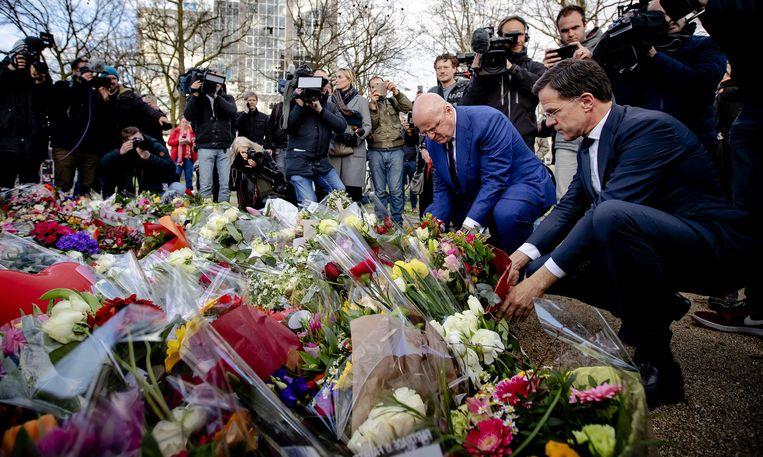 Premier Mark Rutte en minister Ferdinand Grapperhaus van justitie leggen bloemen op het 24 Oktoberplein. Beeld ANP